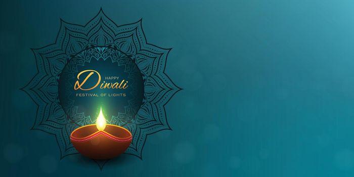 Happy Diwali turquoise background with gold greeting text. Dark mandala decoration behind the lighting diya lamp.