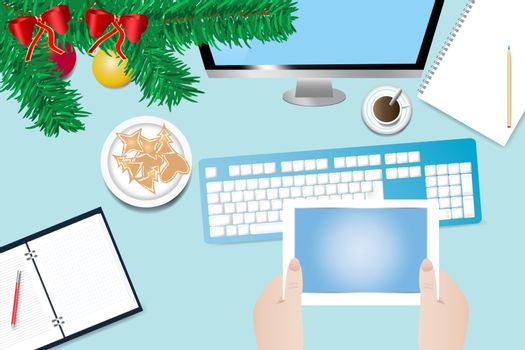 Top view of the office desk withtwig of Christmas tree. Hands are holding a tablet with blank screen ready for your text. All potential trademarks are removed.